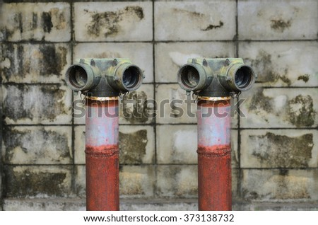 Two red fire hydrant near a cement wall