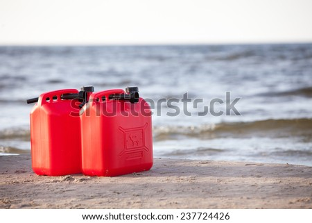Two red fuel cans on the beach - stock photo