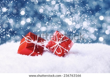 Two red gift boxes in snow on abstract background - stock photo