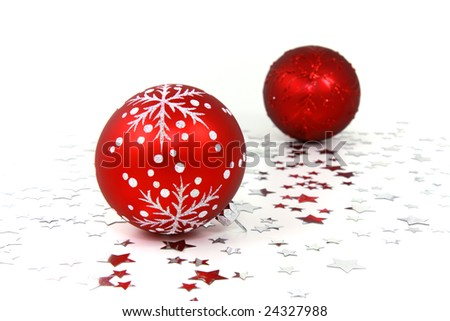Two red glass christmas baubles on white background with silver stars