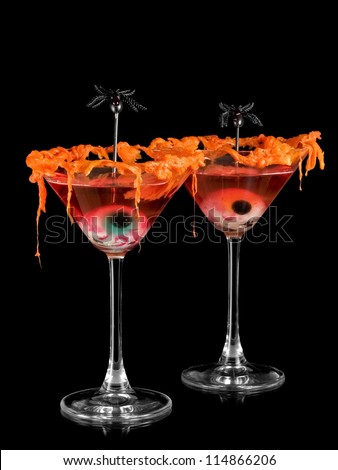 Two red halloween cocktails with eyes and spiders - stock photo