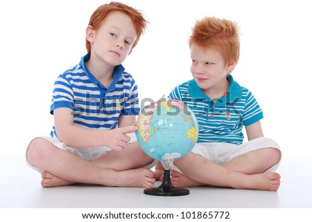 Two red head boy brothers sitting and looking and smiling at geographic world atlas globe isolated on white