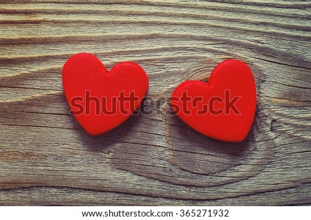Two red heart on a wooden old background. Romantic card. A declaration of love in vintage style. A gift by St. Valentine's Day. Two red heart plasticine