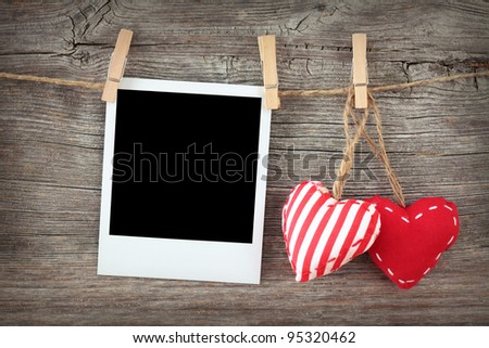 Two red hearts and blank instant photo on clothespin - stock photo