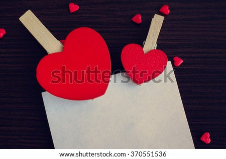 Two red hearts and many small hearts with a piece of paper on the dark wooden background. Empty space for text. Valentines Day background. Valentine's Day theme. - stock photo