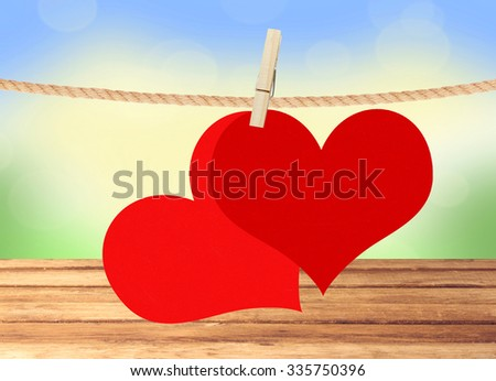 two red hearts hang on clothespin over blurred nature background - stock photo