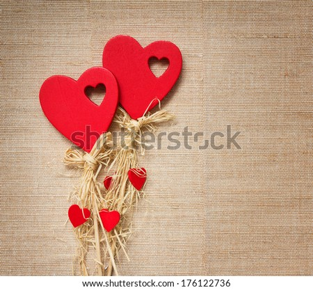 Two red hearts made from natural materials on textile canvas.  - stock photo