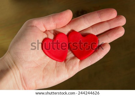 Two red hearts on a female hand