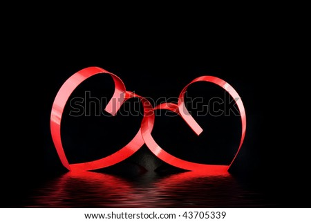 Two red hearts, on black background with  reflection. - stock photo