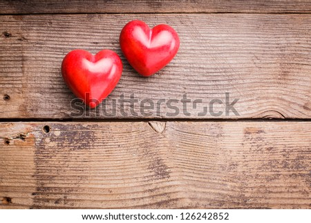 Two red hearts on old shabby wooden background