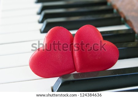 Two red hearts on piano keyboard - stock photo