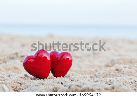 Two red hearts on the beach symbolizing love, Valentine's Day, romantic couple. Calm ocean in the background - stock photo