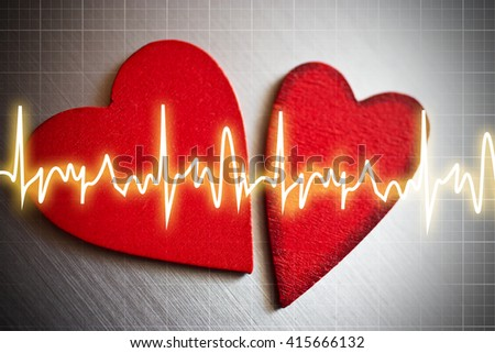 Two red hearts with EKG curve - cardiology examination - stock photo