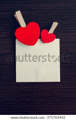 Two red hearts with piece of paper on the dark wooden background. Empty space for text. Valentines Day background. Valentine's Day theme. - stock photo