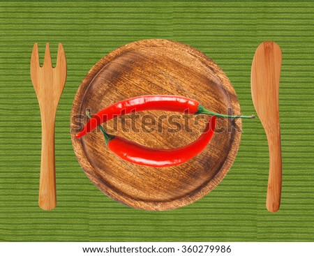Two red hot chilli peppers on wooden plate over green cloth - stock photo