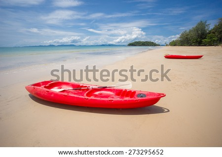 Two red kayaks at the ocean beach during low water - stock photo