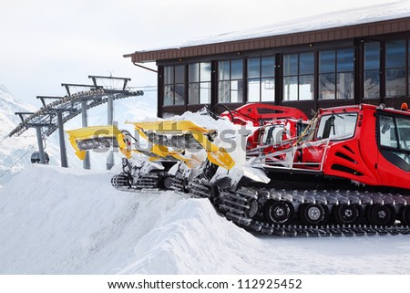 Two red machines for skiing slope preparations in Austrian Alps. - stock photo
