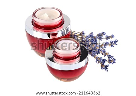 Two red open jars with moisturizing face cream and lavender flowers on a white background