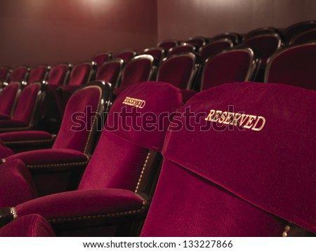 two red reserved theater seats side by side in the middle of others - stock photo