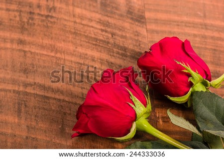 Two red roses on a rough wooden table - stock photo