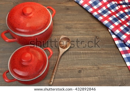 Two Red Saucepan, Wooden Spoon And Checkered Tablecloth On The Rough Rustic Brown Wood Table Background, Top View, - stock photo