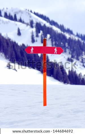 Two red signs for walkers in the snowy mountain - stock photo