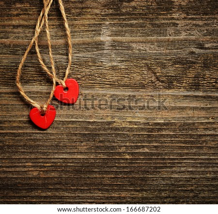 Two red small hearts on a dark wooden background - stock photo