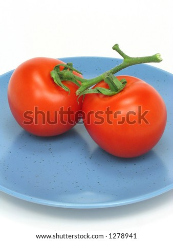 Two red tomatoes on a blue plate on white background