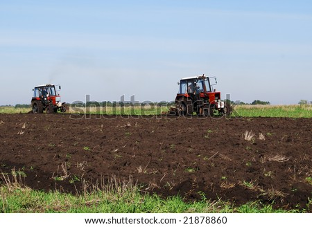 Two red tractors on autumn field against blue sky, black soil ploughed up in the foreground