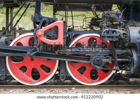 Two red  train wheels of an old steam locomotive on a rusty rails - stock photo