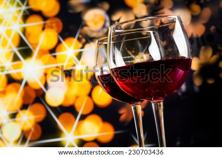 two red wine glasses against golden bokeh lights background, festive and fun concept - stock photo