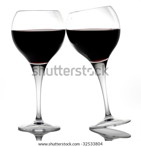 Two red wine glasses making a toast - stock photo