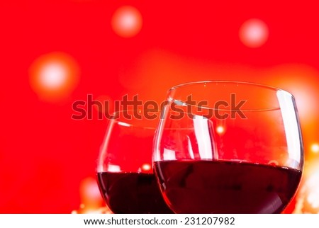 two red wine glasses near the bottle against red lights background, festive and fun concept - stock photo