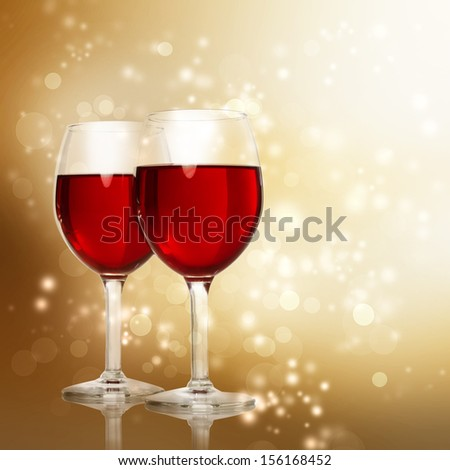 Two Red Wine Glasses on a Gold Sparkling Backdrop - stock photo