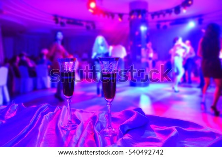 two red wine glasses on foreground and blur abstract at night club party in restaurant on background