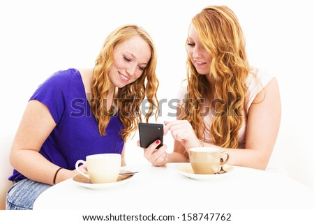 two redhead women sitting at a coffee table busy with a smartphone on white background - stock photo