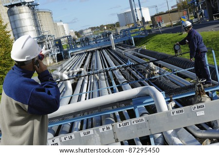 two refinery workers and pipelines - stock photo