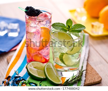 Two refreshing summer cocktails with lime, mint, cranberry on a table - stock photo