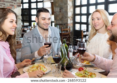 Two relaxed married couple sitting at restaurant table - stock photo