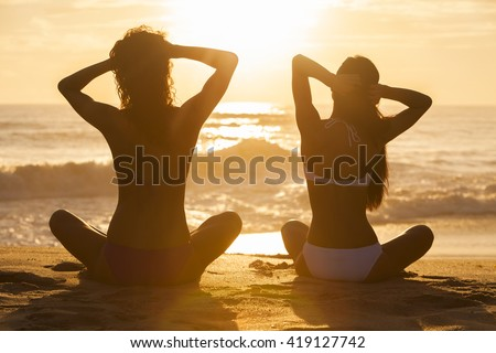 Two relaxed sexy young women or girls wearing a bikini sitting on a deserted tropical beach at sunset or sunrise - stock photo