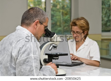 Two researchers working together with a microscope. - stock photo