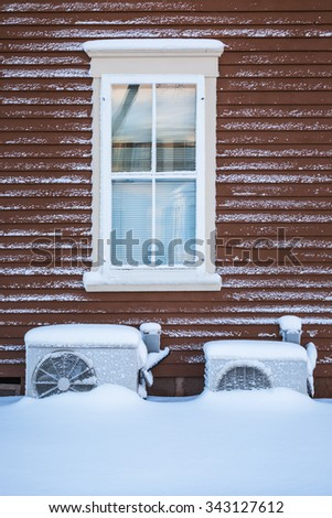 Two residential heat pumps buried in snow. - stock photo