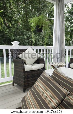 Two resin wicker chairs sit on a covered deck; they have cream colored cushions and pillows;  canvas curtains hang in the background; a white wicker chest serves as a coffee table