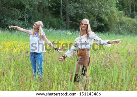 Two retro blonde 1970s hippie girls with sunglasses dancing in field of grass outdoor in nature.