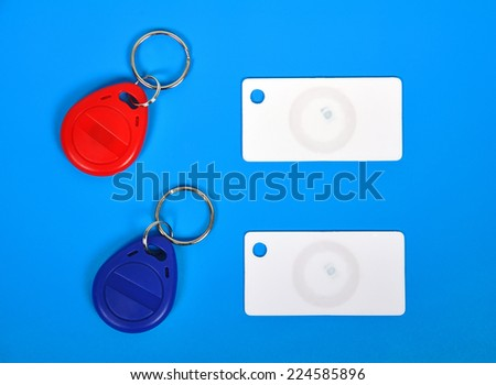 two RFID cards and keychain on a blue background - stock photo