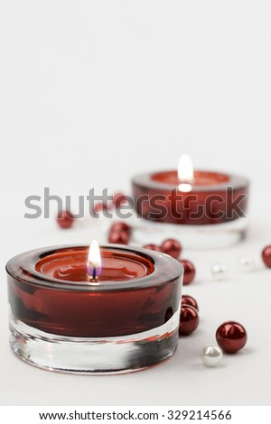 Two rich red glass candle holder votive and red white pearls. White background, vertical, copy space. - stock photo
