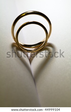 Two rings casting a heart shadow - stock photo