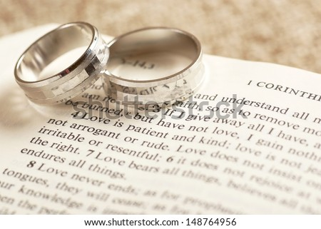Two rings on open Bible - 1. Corinthians chapter 13. - stock photo