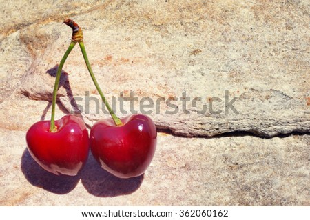 Two ripe berries of sweet cherry on a stone. Romantic couple. Two juicy cherries in the form of heart - stock photo