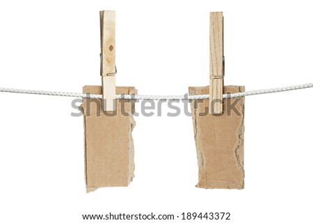 two ripped pieces of card board hanging on one clothespins, isolated on white.